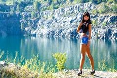 Ungt caucasian le kvinnaanseende på en sjösida i en mountai fotografering för bildbyråer