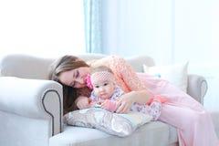 Ungt caucasian modersammanträde med barnet på soffan och bärande rosa färger klär fotografering för bildbyråer