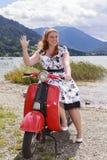 Ungt curvy kvinnasammanträde på en sparkcykel med en klänning och vinka för underkjol Royaltyfri Bild