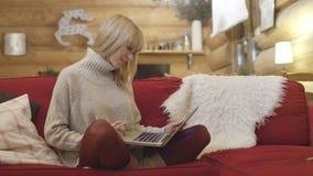 Ungt eftertänksamt kvinnasammanträde på soffan, medan skriva och läsa emails på bärbar datordatoren Arkivfoto