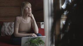 Ungt eftertänksamt kvinnasammanträde på soffan, medan skriva och läsa emails på bärbara datorn med vinterbakgrund på fönstret Arkivbilder