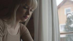 Ungt eftertänksamt kvinnasammanträde på soffan, medan skriva och läsa emails på bärbara datorn med vinterbakgrund på fönstret Royaltyfri Bild