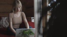 Ungt eftertänksamt kvinnasammanträde på soffan, medan skriva och läsa emails på bärbara datorn med vinterbakgrund på fönstret Arkivfoto