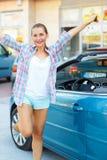 Ungt emotionellt kvinnaanseende nära en cabriolet med tangenterna Arkivfoto