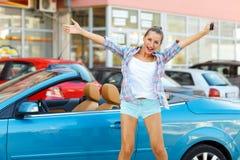 Ungt emotionellt kvinnaanseende nära en cabriolet med tangenterna Royaltyfri Foto