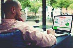 Ungt entreprenörarbete på netbook som dricker kaffe av koppen, medan sitta i modern hotellinre fotografering för bildbyråer