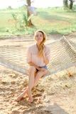 Ungt europeiskt blont sammanträde för kvinnlig person på den vide- hängmattan, sandbakgrund royaltyfri fotografi