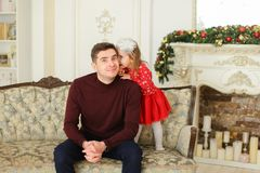 Ungt europeiskt fadersammanträde med den lilla dottern på soffan nära dekorerade spisen Fotografering för Bildbyråer