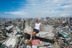 Ungt europeiskt kvinnasammanträde bland avfall på avskrädeförrådsplatsen royaltyfria bilder