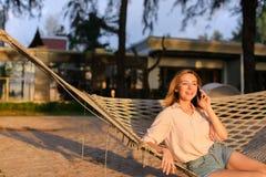 Ungt europeiskt kvinnasammanträde i hängmatta och samtal vid smartphonen, sommarsemestrar royaltyfria foton