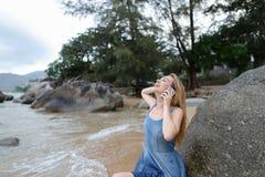 Ungt europeiskt kvinnasammanträde på sand nära havet och stenar som talar vid smartphonen och visar upp tummar fotografering för bildbyråer