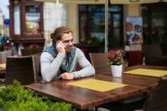 Ungt europeiskt mansammanträde på sreetkafét och samtal vid smartphonen arkivbilder