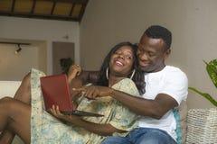 Ungt förälskat tycka om för lyckliga och härliga svarta afrikansk amerikanpar på vardagsrumsoffasoffan med att skratta för bärbar royaltyfria bilder