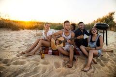 Ungt företag av vänner som jublar som vilar på stranden under soluppgång royaltyfri foto