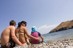 Ungt familjsammanträde på stranden och tycka om deras ferie Fotografering för Bildbyråer