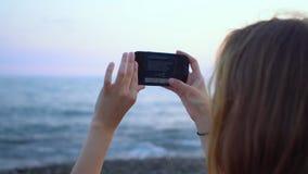 Ungt foto för hipsterkvinnadanande på smartphonen vid havskusten arkivfilmer