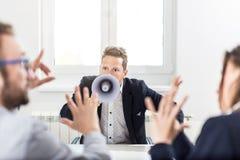 Ungt framstickande som ropar på anställda till och med megafonen i konferensrum royaltyfri fotografi