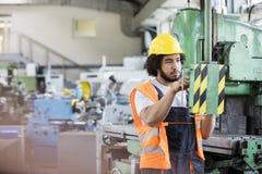 Ungt fungerande maskineri för manuell arbetare i metallbransch Fotografering för Bildbyråer