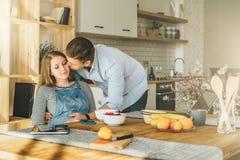 Ungt gift par i kök Gravida kvinnan sitter på tabellen, rymmer kysser mannen hennes gravida buk och Arkivfoto