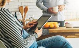 Ungt gift par i köket En gravid kvinna sitter på en tabell och använder en minnestavladator Ett mananseende Royaltyfri Fotografi