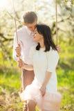Ungt gift par, p? en gunga i en blommig tr?dg?rd eller att parkera Varmt f?r?lskelse-, v?r- och sommarlynne royaltyfri foto