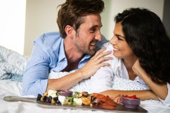 Ungt gift par som äter frukosten i deras säng i sovrum arkivbild