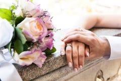 Ungt gift par som rymmer händer på bröllopdag, förälskelse och lycka royaltyfri fotografi