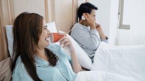 Ungt gift par som spelar med cantelefonen till samtal tillsammans arkivbilder