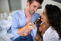 Ungt gift par som ?ter frukosten i deras s?ng i sovrum arkivfoton