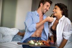 Ungt gift par som ?ter frukosten i deras s?ng i sovrum fotografering för bildbyråer