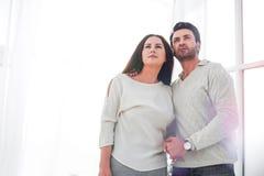 Ungt gift paranseende i ny vardagsrum royaltyfria bilder