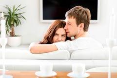 Ungt gift parsammanträde på soffan och den hållande ögonen på tv:n på hom fotografering för bildbyråer