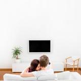 Ungt gift parsammanträde på soffan och den hållande ögonen på tv:n på hom Royaltyfri Fotografi