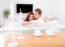 Ungt gift parsammanträde på soffan och den hållande ögonen på tv:n på hom Royaltyfri Foto