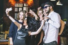 Ungt gladlynt företag av vänner i klubbastången som har gyckel och royaltyfri fotografi