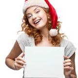 Ungt gladlynt flickaholdingtecken på white Arkivfoto