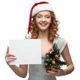 Ungt gladlynt flickaholdingtecken på white Royaltyfri Fotografi