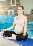 Ungt gravid kvinnasammanträde med ben korsade på mattt Royaltyfria Foton