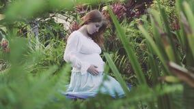 Ungt gravid kvinnasammanträde på knä som kopplar av och tycker om liv i natur lager videofilmer