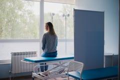 Ungt gravid kvinnasammanträde på säng i bekvämt avvärjer och att vänta på doktorn hänsynsfullt arkivfoton