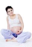 Ungt gravid kvinnasammanträde på soffan. se kameran. Royaltyfri Bild