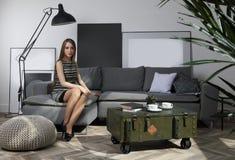Ungt gulligt flickasammanträde på soffan i vardagsrum royaltyfri fotografi