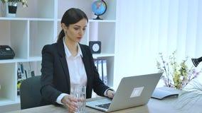 Ungt härligt affärskvinnadricksvatten på arbete arkivfilmer