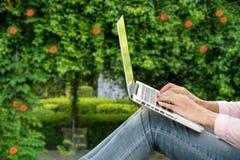 Ungt härligt arbeta för kvinna som är utomhus- i ett offentligt, parkerar bärbar dator som fungerar utomhus Kantjusterad bild av  royaltyfri bild