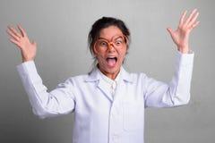 Ungt härligt asiatiskt agera för kvinnadoktor som är galet, medan bära krimskramsexponeringsglas royaltyfri foto