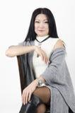 Ungt härligt asiatiskt kvinnasammanträde på en stol på en ljus bakgrund Arkivfoto