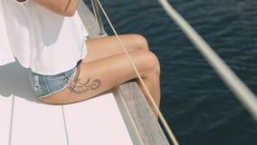 Ungt härligt brunettflickasammanträde på yachten Royaltyfri Foto