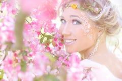 Ungt härligt elegant attraktivt flickaanseende i en skog nära blomningträd med långt hår som är blont i solig dag och makeup Royaltyfria Foton