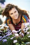 Ungt härligt flickagrannhuset med purpura blommor Arkivfoto