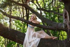 Ungt härligt flickasammanträde på ett stort träd i sommar parkerar Fotografering för Bildbyråer